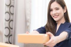 Vrouw die pakketdoos voor post en verzending overhandigen royalty-vrije stock afbeeldingen