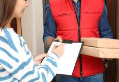 Vrouw die pakketten van de koerier van de leveringsdienst binnen ontvangen royalty-vrije stock afbeeldingen