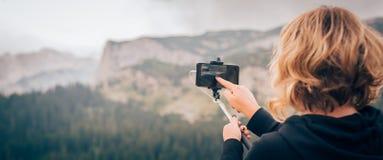 Vrouw die panoramisch beeld van berglandschap nemen Selfiepho stock afbeelding