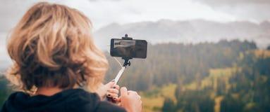 Vrouw die panoramisch beeld van berglandschap nemen Selfiepho stock fotografie