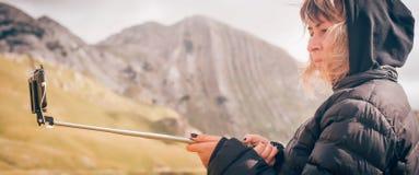 Vrouw die panoramisch beeld van berglandschap nemen Selfiepho stock foto