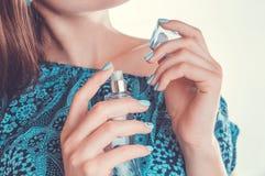 Vrouw die parfum op haar pols toepast stock foto's