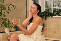 Vrouw die perfum in de badkamers gebruikt Royalty-vrije Stock Foto's