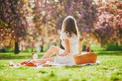 Vrouw die picknick op zonnige de lentedag hebben in park tijdens het seizoen van de kersenbloesem stock fotografie