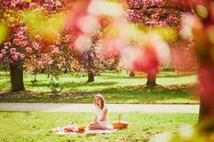Vrouw die picknick op zonnige de lentedag hebben in park tijdens het seizoen van de kersenbloesem royalty-vrije stock fotografie