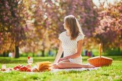 Vrouw die picknick op zonnige de lentedag hebben in park tijdens het seizoen van de kersenbloesem stock foto