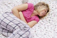 Vrouw die in pijn op het bed kronkelen die haar buik houden royalty-vrije stock fotografie