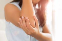 Vrouw die pijn in verwonde elleboog hebben Gezondheidszorg en het concept van de wapenpijn stock afbeelding