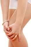 Vrouw die pijnlijke knie houdt Stock Afbeelding