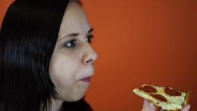 Vrouw die pizza, close-up op oranje achtergrond eten Het wijfje geniet van een heerlijke maaltijd stock videobeelden