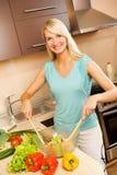 Vrouw die plantaardige salade mengt Stock Afbeeldingen