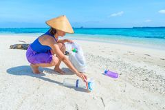 Vrouw die plastic flessen op mooi tropisch strand, turkooise overzees, zonnige dag, concept van het recyclingsvuilnis verzamelen, royalty-vrije stock afbeeldingen