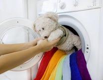 Vrouw die pluizig stuk speelgoed van wasmachine nemen stock foto's