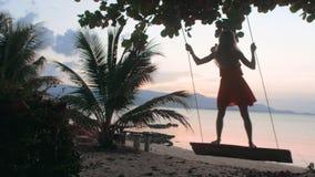 Vrouw die pret hebben, die op de schommeling op zonsondergang spelen stock videobeelden