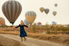 Vrouw die Pret met Vliegende Hete Luchtballons hebben op Achtergrond stock afbeeldingen