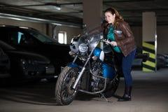 Vrouw die proberen op motorfiets te zitten, die zich in donker parkeren bevinden royalty-vrije stock foto