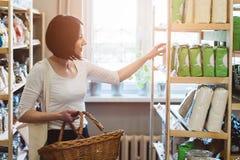 Vrouw die producten in ecologische winkel kiezen stock foto's