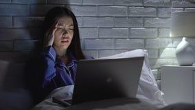 Vrouw die project op laptop doen die laat thuis, aan hoofdpijn lijden aan overwerken stock videobeelden