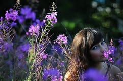 Vrouw die Purpere Bloemen ruikt royalty-vrije stock afbeelding
