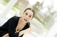 Vrouw die rechtstreeks vooruit met potloodeind staren in mond Stock Afbeeldingen
