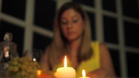 Vrouw die in Restaurant die door Kaarslicht dineren, op de Telefoon, het Drinken Wijn spreken stock footage