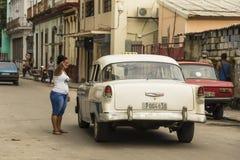 Vrouw die richting richten aan uitstekende Chevy-taxi Havana stock afbeelding
