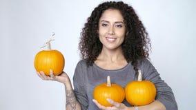 Vrouw die rijpe oranje pompoenen houden stock videobeelden