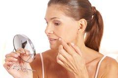 Vrouw die rimpels in spiegel controleert Royalty-vrije Stock Foto
