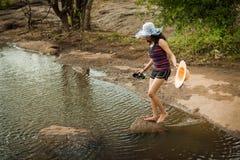 Vrouw die rivier kruist Stock Foto's