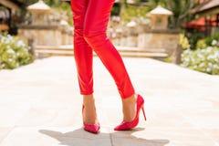 Vrouw die rode broek en hoge hielen dragen royalty-vrije stock fotografie