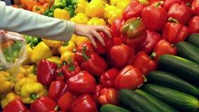 Vrouw die rode en gele peper in kruidenierswinkelopslag selecteren