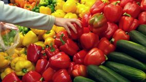 Vrouw die rode en gele peper in kruidenierswinkelopslag selecteren stock video