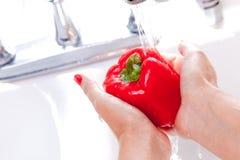 Vrouw die Rode Groene paprika wast stock afbeelding