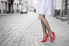 Vrouw die rode hoge hielschoenen in stad dragen stock afbeelding