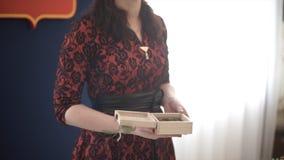 Vrouw die in rode kleding een houten doos houden De aantrekkelijke vrouw kleedde zich in rood dat een speciaal heden aanbiedt Geï royalty-vrije stock foto's