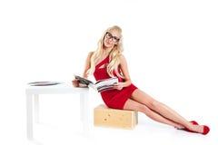 Vrouw die in rode kleding een tijdschrift houden Stock Foto's