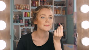 Vrouw die rode lippenstift zet die in spiegel kijkt Make-up bij nacht die klaar alvorens naar partij te gaan worden Royalty-vrije Stock Afbeelding