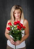 Vrouw die rode rozen kijken royalty-vrije stock fotografie