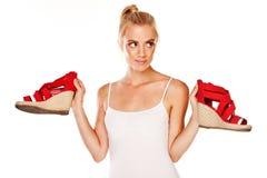 Vrouw die rode sandals houdt Royalty-vrije Stock Foto's