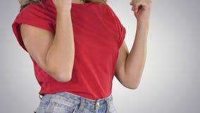 Vrouw die in rode t-shirt gebaren maken terwijl het spreken op de telefoon op gradiëntachtergrond stock footage