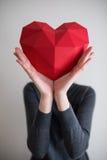 Vrouw die rode veelhoekige document hartvorm tonen Stock Afbeeldingen
