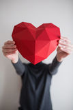 Vrouw die rode veelhoekige document hartvorm tonen Stock Foto