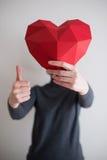 Vrouw die rode veelhoekige document hartvorm tonen Royalty-vrije Stock Afbeeldingen