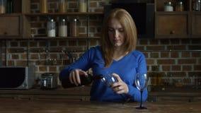 Vrouw die rode wijn gieten in glazen in de keuken stock video
