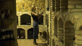 Vrouw die rode wijn van glas drinken en fles houden in kelder in hand Vrouwen winemaker proevende rode wijn van glas binnen stock video