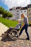 Vrouw die rolstoelgebruiker helpt Royalty-vrije Stock Afbeeldingen