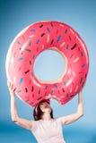 Vrouw die rond met vlotterring voor de gek houden in vorm van doughnut Royalty-vrije Stock Fotografie