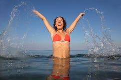Vrouw die rood badpak draagt dat in overzees springt stock foto