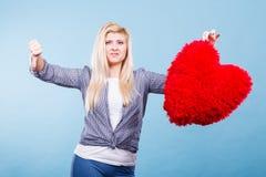 Vrouw die rood hart houden die duim neer tonen Stock Fotografie