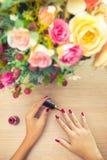 Vrouw die rood poetsmiddel op spijkers toepassen Ontspan, zorg en schoonheidsconcept stock foto